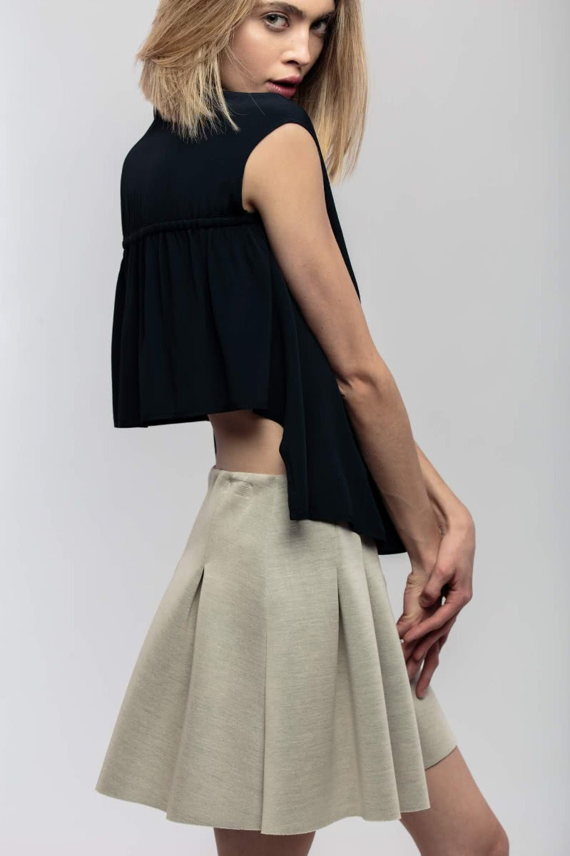 Asymmetrical blouse, the back part being shorter than the front. The blouse closes with buttons in the front. 100% polyester voile in a dark blue fabric.