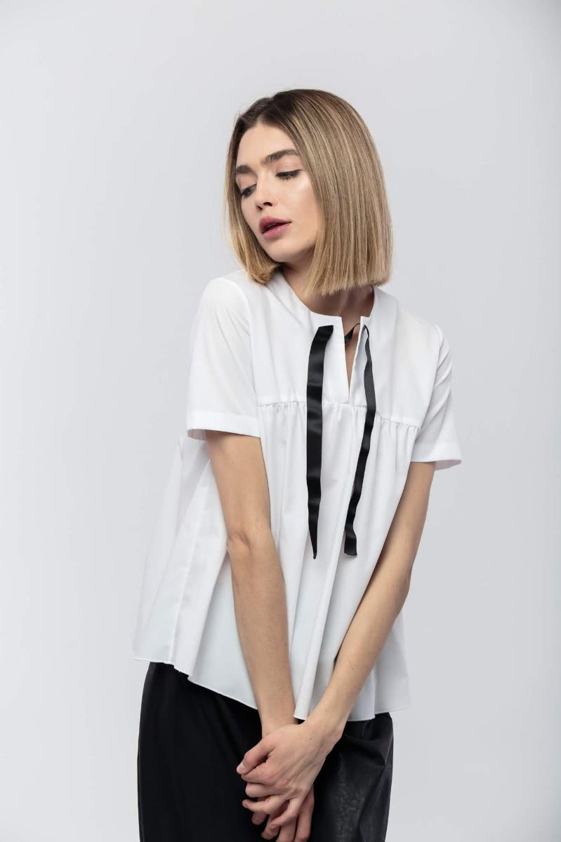 White blouse (100% cotton)in a wide fit, short sleeves and an ornamental black satin band in the front.